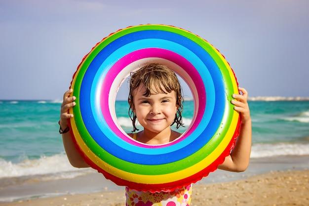 Ein kind schwimmt in einem schwimmbad mit einem rettungsring. Premium Fotos
