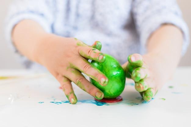 Ein kind setzt ein grünes osterei auf einen stand mit seinen händen, die mit farbe auf einer weißen tabelle befleckt werden. Premium Fotos