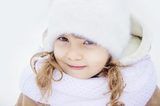 Ein kind spielt im schnee im winter. selektiver fokus Premium Fotos