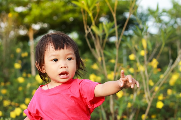 Ein kindermädchen, das ihren finger nach links auf den garten zeigt. Premium Fotos