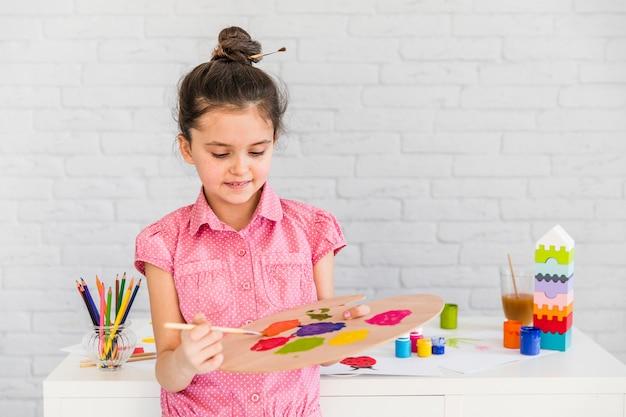 Ein kindermädchenkünstler, der das aquarell auf palette mischt Kostenlose Fotos