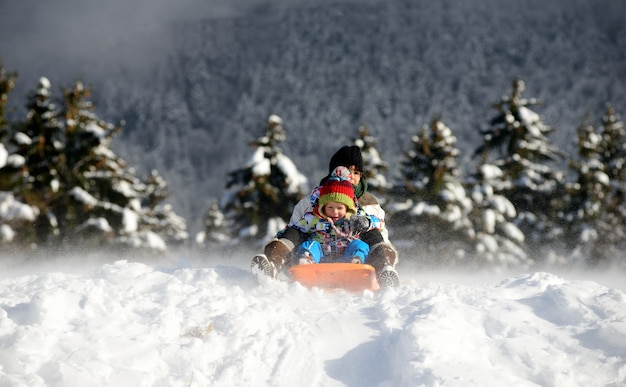 Ein kleiner junge, der im schnee rodelt Premium Fotos