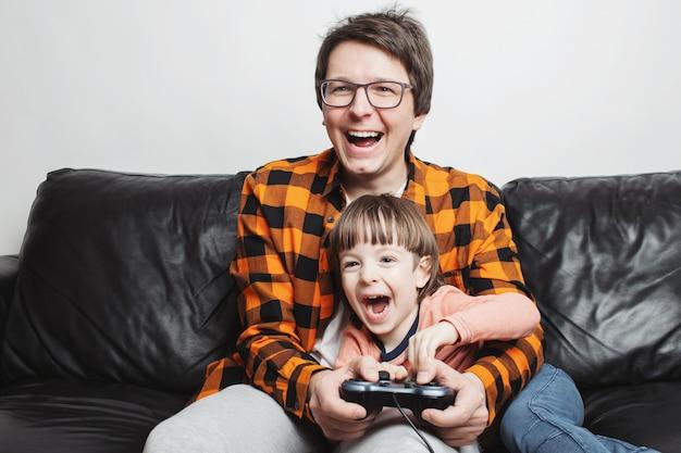 Ein kleiner junge, der videospiele mit vati spielt. Premium Fotos