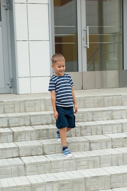 Ein kleiner junge geht alleine, verlässt das gebäude und geht die stufen hinunter Premium Fotos