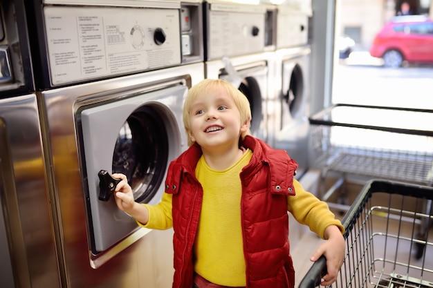 Ein kleiner junge lädt kleidung in die waschmaschine im öffentlichen waschsalon Premium Fotos