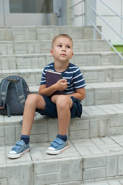 Ein kleiner junge sitzt auf den stufen der schule, hält notizbücher in der hand und schaut zum himmel hoch Premium Fotos