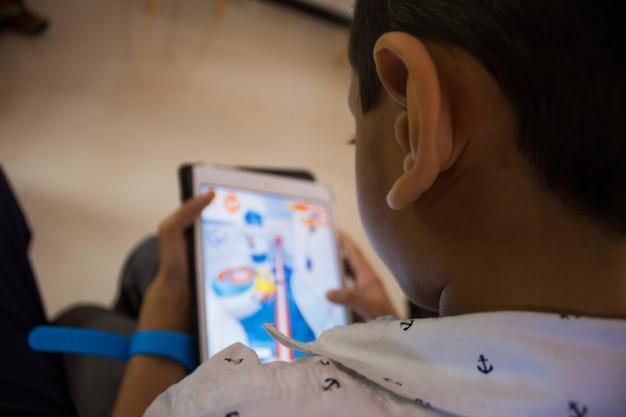 Ein kleiner junge spielt ein spiel auf seinem tablet Kostenlose Fotos
