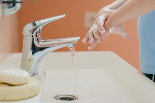 Ein kleiner junge wäscht sich im bad mit seife die hände. Premium Fotos