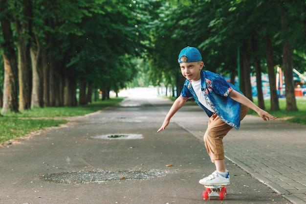 Ein kleiner stadtjunge andskateboard. ein junger mann fährt auf einem parka-skateboard Premium Fotos
