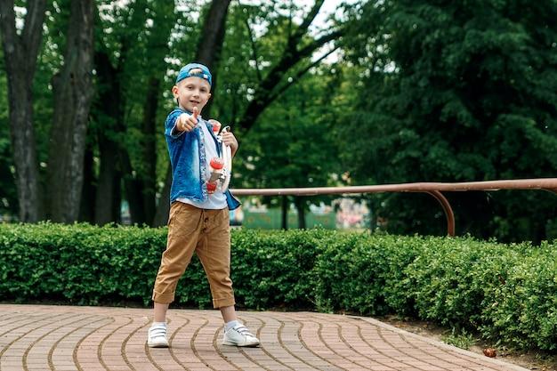 Ein kleiner stadtjunge und ein skateboard. ein junger mann steht im park und hält einen skateboar in der hand Premium Fotos