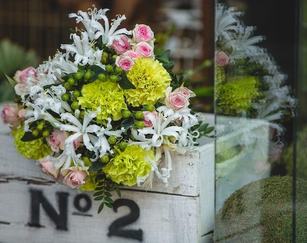 Ein kleiner und hübscher blumenstrauß von bunten blumen innerhalb einer weißen holzkiste Kostenlose Fotos