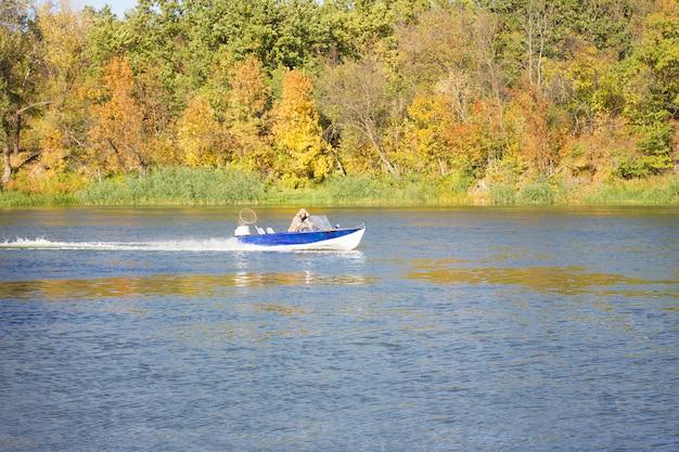Ein kleines boot schwimmt auf dem herbstfluß. fischer segeln auf einem boot Premium Fotos