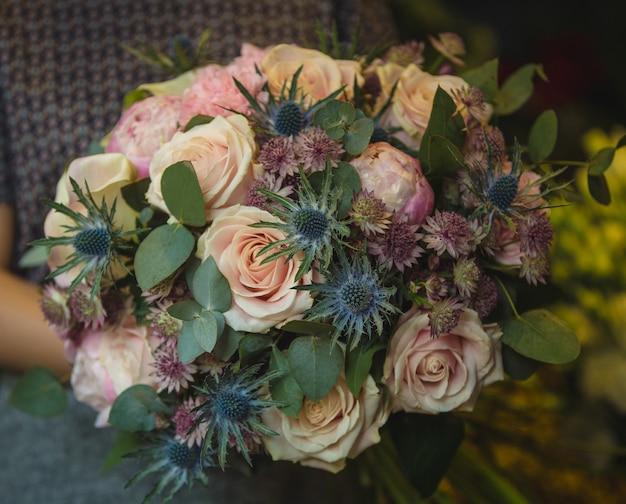 Ein kleines bündel rosa rosen und dekorative blumen in den händen einer frau. Kostenlose Fotos