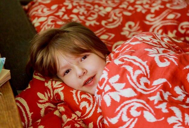 Ein kleines krankes mädchen im schlafzimmer. kleines mädchen, das auf einem bett trägt pyjamas sitzt. Premium Fotos