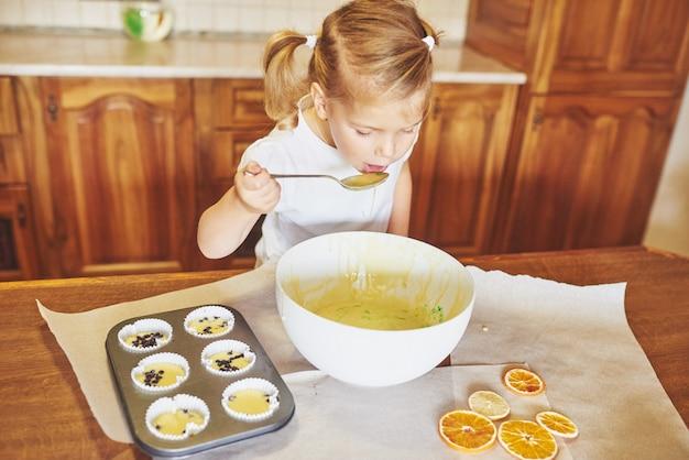 Ein kleines mädchen bereitet einen teig für muffins vor. Kostenlose Fotos