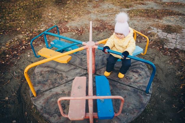 Ein kleines mädchen, das auf dem spielplatz der stadt der kinder spielt. ein kleines kind reitet den hügel hinunter, klettert auf dem karussell die seile hoch. unterhaltungsindustriekonzept, familientag, parks der kinder Premium Fotos