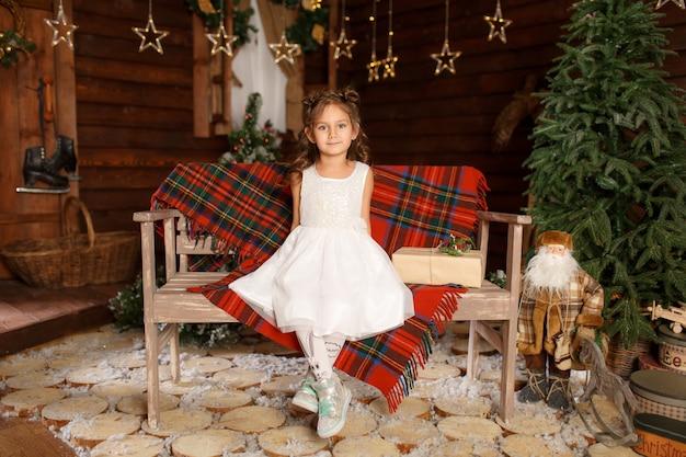 Ein kleines mädchen im weißen kleid, das auf der bank sitzt. Premium Fotos