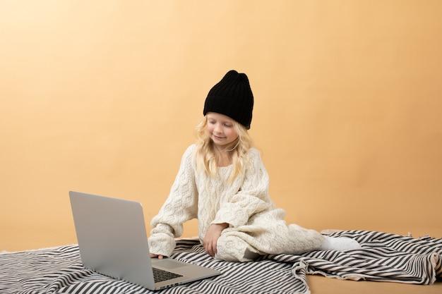 Ein kleines mädchen in einem weißen strickkleid und einem schwarzen hut sitzt auf einem plaid auf einem gelb. Premium Fotos