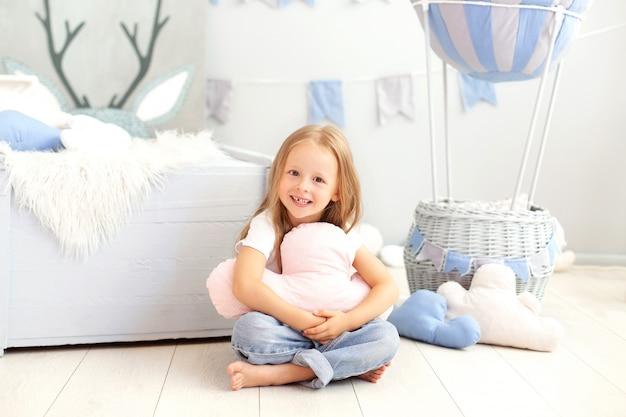 Ein kleines mädchen in freizeitkleidung hält ein wolkenkissen an die wand eines dekorativen ballons. das kind spielt im kinderzimmer. das konzept der kindheit, reisen. geburtstag, feiertagsdekorationen Premium Fotos
