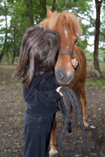 Ein kleines mädchen küsst sich und ihr reinrassiges shetlandpony Premium Fotos