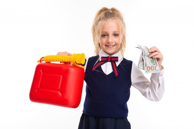 Ein kleines mädchen mit blonden haaren in einem pferdeschwanz hält geld und eine spielzeugdose Premium Fotos