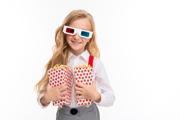 Ein kleines mädchen mit langen blonden haaren in ihrer brille 3-d mit popcorn. Premium Fotos