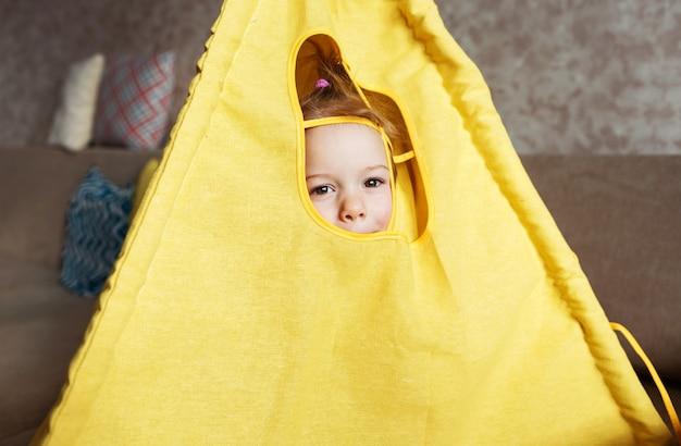 Ein kleines mädchen schaut aus dem fenster eines tipis und spielt zu hause auf der couch. kinderspiele zu hause. Premium Fotos