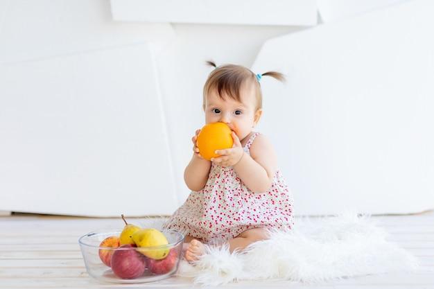 Ein kleines mädchen sitzt in einem hellen raum mit einem obstteller und isst eine orange Premium Fotos