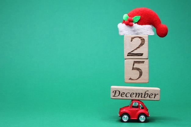 Ein kleines rotes spielzeugauto mit dem 25. dezember auf holzklötzen und einer weihnachtsmütze darüber. Premium Fotos