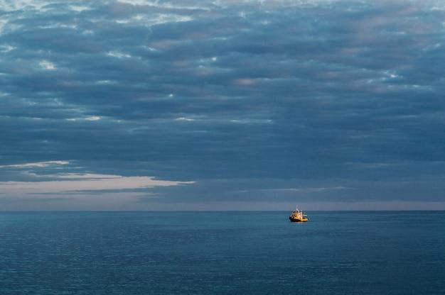 Ein kleines schiff auf see gegen den sonnenuntergangshimmel. Premium Fotos