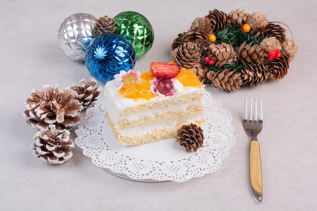 Ein köstliches stück kuchen mit tannenzapfen auf weißem hintergrund. hochwertiges foto Kostenlose Fotos