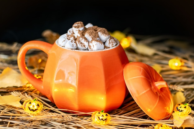 Ein kürbisförmiger becher mit einem heißen getränk, schokolade oder kakao und marshmallows auf einem tisch mit heu, einer halloween-kürbislaternengirlande und trockenen blättern. herbststillleben mit warmer, gemütlicher beleuchtung. Premium Fotos