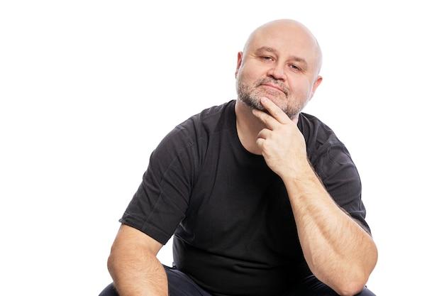 Ein lächelnder kahler mann mittleren alters in einem schwarzen t-shirt sitzt. isoliert weiß Premium Fotos