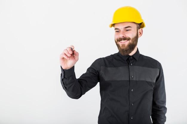 Ein lächelnder männlicher architekt, der gelben hardhatbehälter für das schreiben trägt Kostenlose Fotos