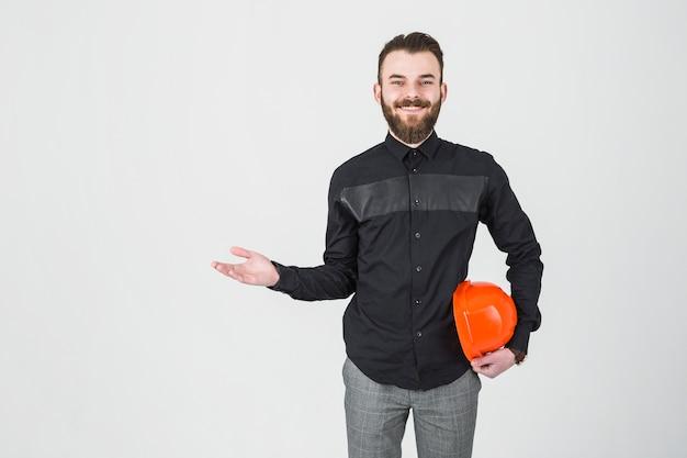 Ein lächelnder männlicher ingenieur, der den hardhat achselzuckend hält Kostenlose Fotos