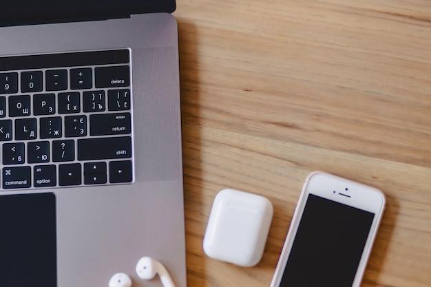Ein laptop, ein telefon und ein drahtloser kopfhörer auf einem holztisch Premium Fotos