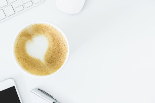 Ein lattekaffee mit kunstherzmilch auf der weißen schreibtischtabelle vom draufsicht- und kopienraum. flache lage mit schreibtisch-, geschäfts- und valentinsgrußkonzept. Premium Fotos