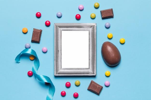 Ein leerer leerer weißer silberner rahmen, der mit osterei umgeben ist; edelstein-bonbons und schokoladenstücke auf blauem hintergrund Kostenlose Fotos