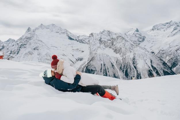 Ein liebendes paar im winter im schnee. kuss im schnee in den bergen. Premium Fotos