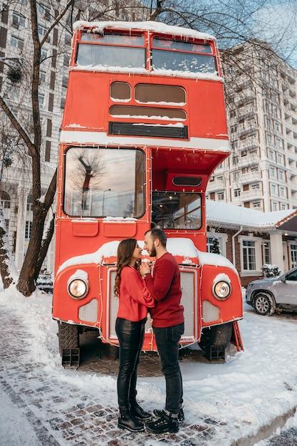 Ein liebendes paar umarmt den hintergrund eines roten busses. valentinstag. hochwertiges foto Premium Fotos
