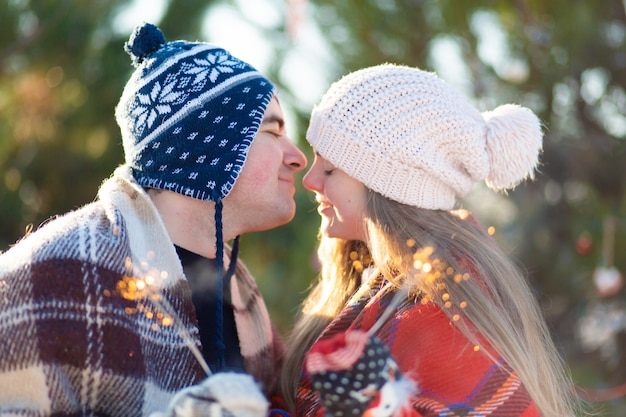 Ein liebespaar in warmen plaids küsst wunderkerzen in den händen. Premium Fotos