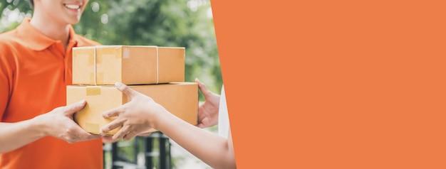 Ein lieferbote in einem orangefarbenen polohemd, das einem kunden ein paket gibt Premium Fotos