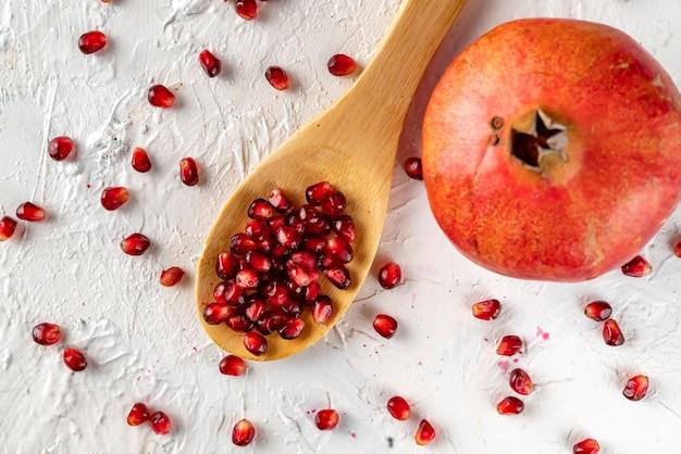 Ein löffel mit granatapfelfrucht flach auf den tisch gelegt mit samen und körnern flach auf den tisch gelegt Premium Fotos