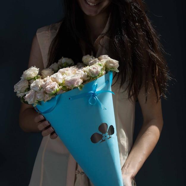 Ein mädchen, das einen blauen pappblumenstrauß von weißen rosen in den händen auf einer grünen wand hält Kostenlose Fotos