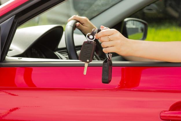 Ein mädchen in einem roten auto demonstriert die schlüssel zu einem neuen auto, das konzept des kaufens eines fahrzeugs Premium Fotos