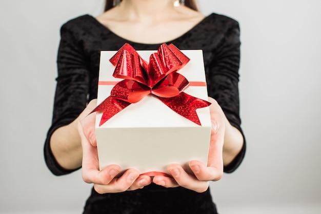 Ein mädchen in einem schwarzen kleid hält ein weißes geschenk mit einer roten schleife. Premium Fotos
