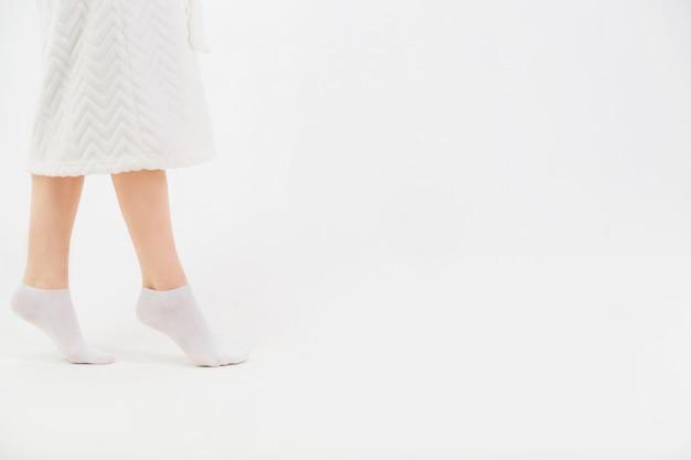 Ein mädchen in einem weißen bademantel und socken zieht sich nach dem duschen die socken an. nahaufnahme von schönen weiblichen schlanken beinen. seitenansicht. Premium Fotos