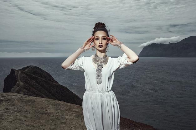 Ein mädchen in einem weißen kleid und schmuck steht auf einer klippe Premium Fotos