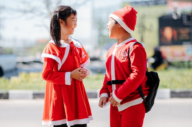 Ein mädchen in sandigem outfit und ein junge in santa-outfit spielen fröhlich. Premium Fotos