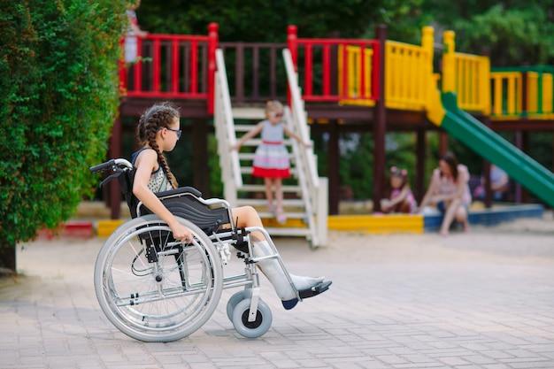 Ein mädchen mit einem gebrochenen bein sitzt im rollstuhl vor dem spielplatz. Premium Fotos